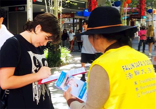 '图1~4:法轮功学员在莫里街购物中心前讲真相,呼吁民众签名反迫害。'