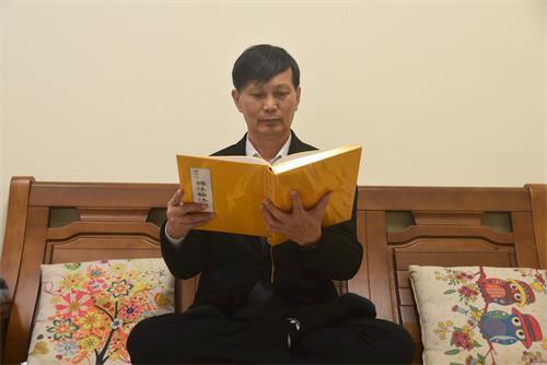 '图2:廖伟辰在读法轮大法书籍,表示他已拥有生命中最珍贵的财富。'