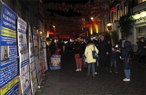 '图4~5:夜幕降临伦敦唐人街,法轮功学员继续展示真相,引发更多民众关注。'