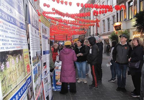 '图6:二零二零年二月一日,从剑桥来伦敦游览的苏珊(Susan)和伊恩(Inn)夫妇(图右正在观看展板两人)在伦敦唐人街驻足了解法轮功真相'
