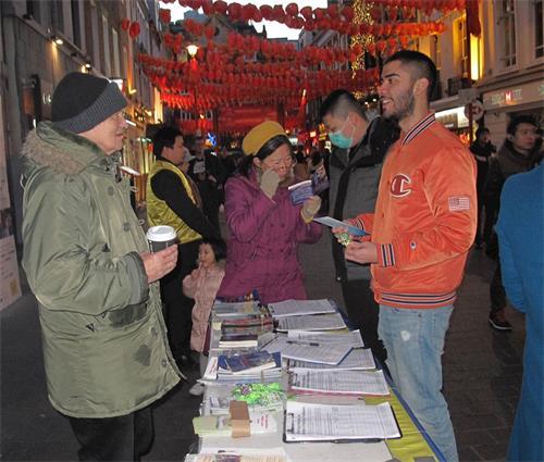 '图8:二零二零年二月一日,在伦敦唐人街,法轮功学员把«九评共产党»一书和«共产主义的终极目的»报纸送给一位在英国攻读政治学学位的台湾留学生(戴口罩者)。'