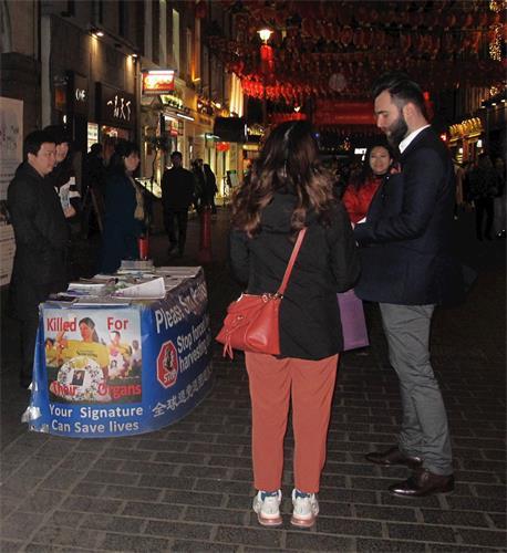 '图9:二零二零年二月一日,在伦敦工作的罗马尼亚人迈克尔(Michael,最右边站立者)在伦敦唐人街驻足了解法轮功真相并签名支持法轮功学员反迫害。'