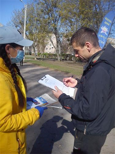 '图1~2:哈尔科夫市民经过炼功场地或和学员交谈,或签名支持法轮功'