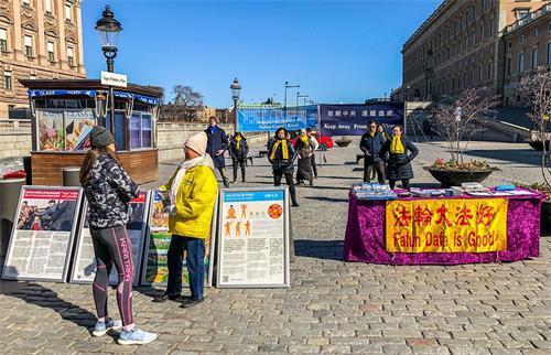 '图1:瑞典法轮功学员在斯德哥尔摩市中心国会大厦旁的钱币广场(Mynttorget),举办讲真相活动。'