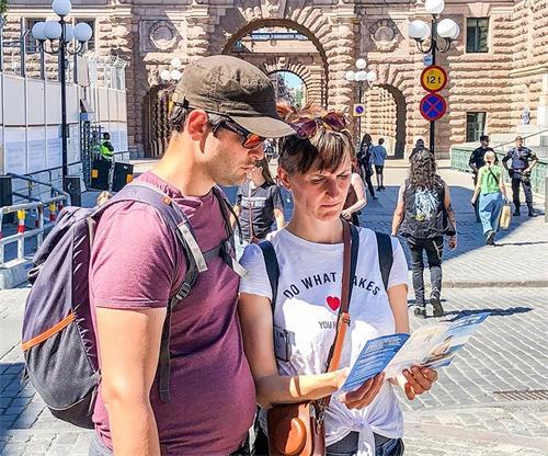 '图7:来自德国的年轻夫妇得到了一张德文的大法真相传单,俩人站在那里仔细的阅读,主动了解法轮功真相,'