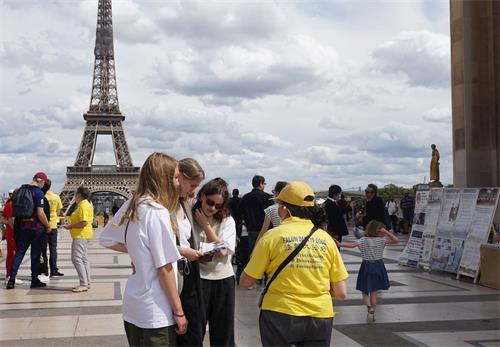 '图10:游客在和法轮功学员交流'