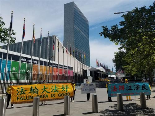 '图3:多名亲属和王晶站在一起来到联合国总部前,曝光中共邪恶'
