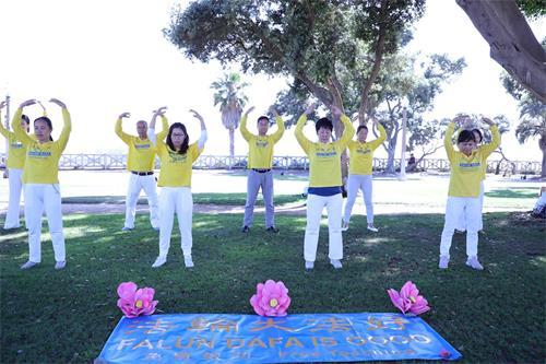 '图2~3:在遵守当地政府在疫情期间的相关规定的前提下,洛杉矶部份法轮功学员在圣莫妮卡码头公园炼功,传播法轮功的真相。'