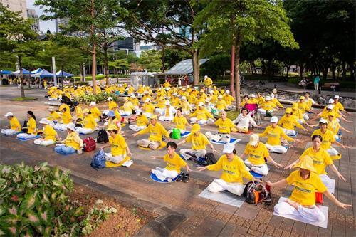 '圖15:臺北市市府廣場旁草地上還有二百多人展示法輪功五套優美功法。'