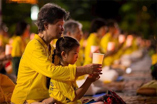 '图1~3:法轮功学员在台北市政府广场前举办反迫害21周年烛光悼念活动。'