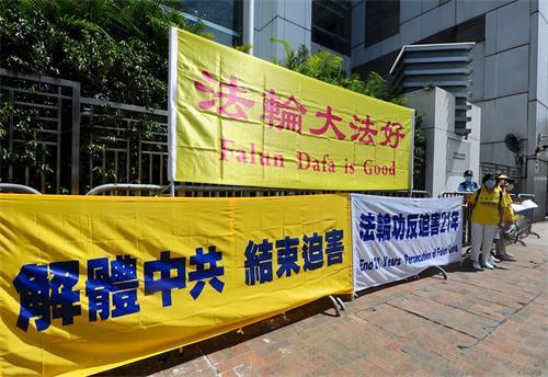 """'图1~3:香港法轮功学员无惧""""港版国安法""""压力,二零二零年七月十九日到中联办前抗议,促解体中共、结束迫害。'"""