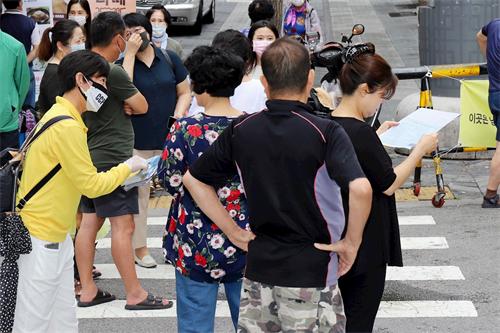 '图24:法轮功学员在韩国首尔街上派发简介,让市民了解真相。'