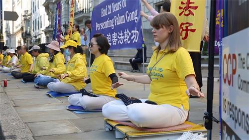 '图6:二零二零年七月二十日,英国法轮功学员尤丽雅(Yulia,右)参加在伦敦中共使馆前的集体炼功'