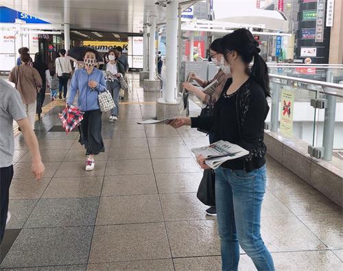 '图3:法轮功学员在柏车站派发法轮功真相资料'