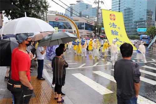 '图10~11:14:在韩国华人聚居地举行的声援3.6亿中国人三退大游行,民众在聚精会神在观看游行。'
