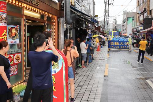 '图12:民众拿起手机在拍照游行队伍。'