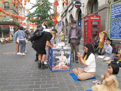 '图7:二零二零年八月十六日,三位意大利青年在伦敦唐人街签名支持法轮功反迫害'