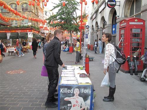 '图9:二零二零年八月十六日,在伦敦唐人街,英国女演员爱琳(EileenVonSkopnik)看到两位青年走近法轮功信息台,她走上前去鼓励他们签名支持法轮功反迫害'