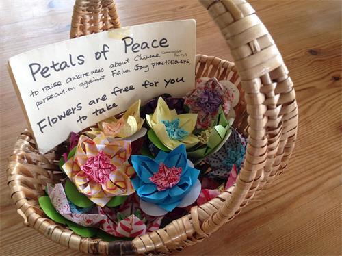 '图5:现场教儿童叠置手工莲花并免费发放,是英国康沃尔地区法轮功学员多年来一直采用的一个弘法讲真相方式,法轮功学员罗斯(Rose)刚刚制作了一些手工莲花。'