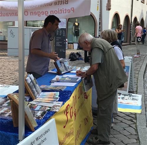 '图1~7:二零二零年九月十九日,部份德国法轮功学员在旅游名城弗莱堡市中心的市政厅广场举办了信息日活动。很多民众驻足签名支持法轮功发迫害。'