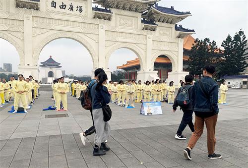 '图1~2:被疫情笼罩的台北市,法轮功学员集体炼功散发的祥和能量场吸引前来自由广场的游客驻足拍照,拍下这珍贵的场面。'