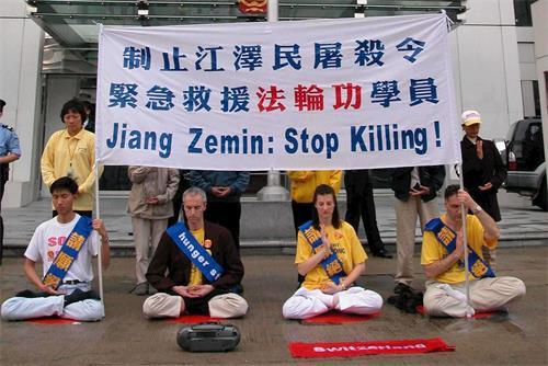 '图2:二零零二年三月十四日,四名瑞士和十二名香港的法轮功学员在西区中联办前绝食静坐,抗议中共迫害残杀大陆法轮功学员,遭警方武力粗暴抬走。(明慧网)'