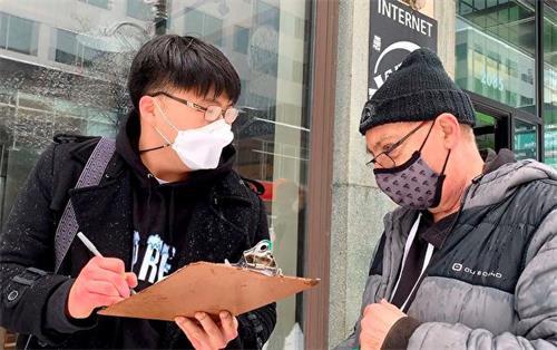 '图9:韩国青年(左)非常赞同游行传递的信息,在呼吁制裁中共的征签板上签字。'