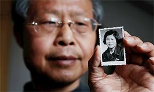 '张红兵手举母亲的照片(网络图片)'