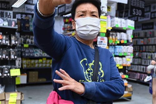 '图1~2:在香港旺角到处放置诬蔑法轮功展示架的老妇,被发现后自曝听命于深圳共产党。'