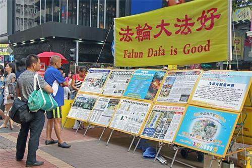 '图6~7:香港街头讲真相的法轮功学员无所畏惧,风雨无阻的传递真相,从未停歇。'