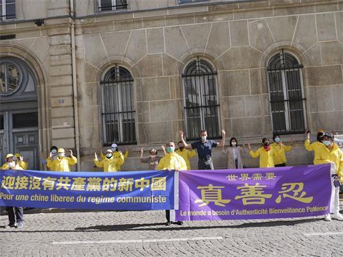 '图1~2:法轮功学员在巴黎中使馆前举行集会,告诉人们法轮功<span class='voca' kid='62'>真相</span>,揭露中共二十多年来对法轮功的残酷迫害。'