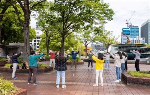 '图1:法轮功学员在日本名古屋市(Nagoya-City)中心的繁华地段炼功,向民众介绍<span class='voca' kid='86'>功法</span>。'