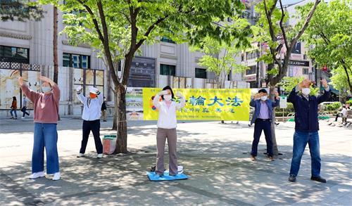 '图5:韩国法轮功学员在驻韩中共大使馆附近集体炼功。'