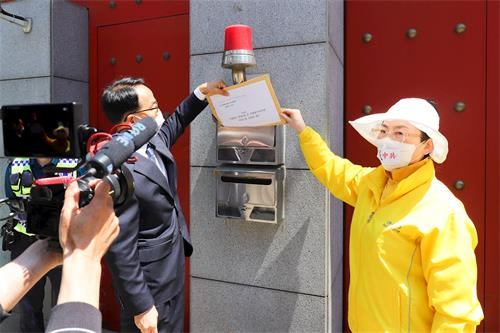 '图6:记者会结束时,韩国法轮大法佛学会代表将声明书投入驻韩中共大使馆的信箱。'