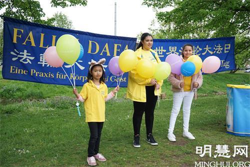 '图3:大法小弟子萨拉(SaraK.,中)和其他孩子一起参加了2021年5月13日在纽伦堡沃德湖畔的法轮大法日庆祝活动。'