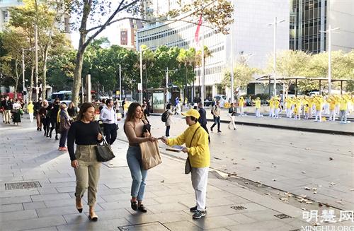 图1~2:匆匆赶着上班的主流人士被一片祥和的场面吸引,悉尼法轮功学员正迎着朝霞集体晨炼