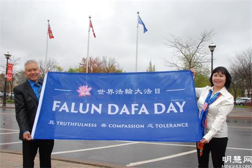 '图13:当地的越南裔法轮功学员阮海伦(HelenThieu)和先生到场庆祝升旗。'