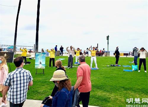 '图1~2:在刚过去的是美国阵亡将士纪念日(MemorialDay)长周未,法轮功学员来到加洲橙县的拉古娜海滩(LagunaBeach)炼功洪法、传播法轮功<span class='voca' kid='62'>真相</span>。'
