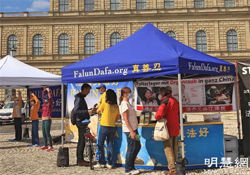 '图1~2:二零二一年五月二十九日,法轮功学员在慕尼黑马克西——约瑟夫广场(Max-Joseph-Platz)举办讲<span class='voca' kid='62'>真相</span>活动,不少民众驻足了解。'
