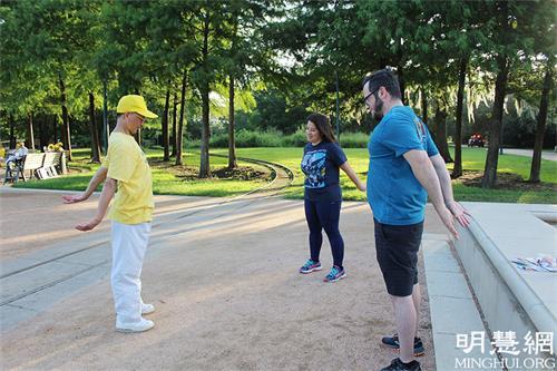 图3:学员王先生(左一)教让内夫妇炼功动作