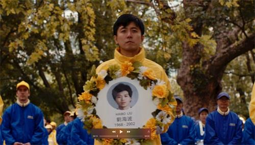 '图3:《永恒的五十分钟》剧照,每个扮演者手持自己扮演的学员遗照。图为穆川捧着刘海波遗照'