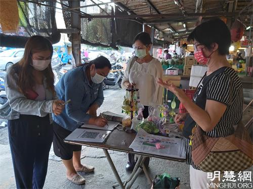 图1:法轮功学员在云林虎尾黄昏市场讲真相发送莲花书签及真相资料。