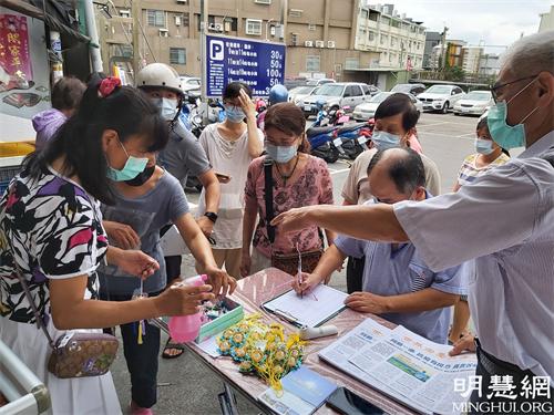 图2-4:法轮功学员在云斗六黄昏市场讲真相发送莲花及真相资料。