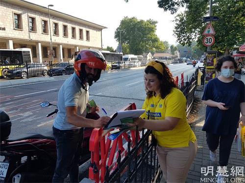 '图9:一位骑摩托车的男士停下来在要求解体中共的请愿信上签字'