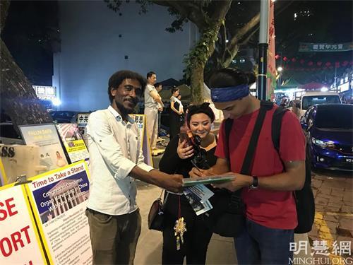 '图9:索马里人(左)主动用阿拉伯语帮忙讲真相,明白真相的游客在制止迫害的征签表上签名。'