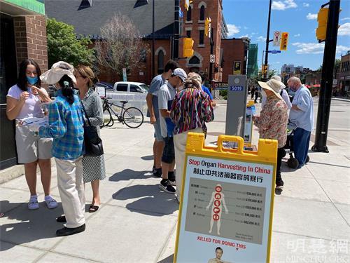 '图1~2:渥太华人在市中心的街道上,通过签名等方式表达对法轮功的支持。'