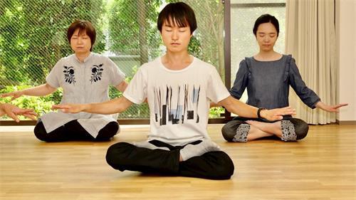 '图1:日本法轮功学员落合辉(中))炼法轮功第五套功法'