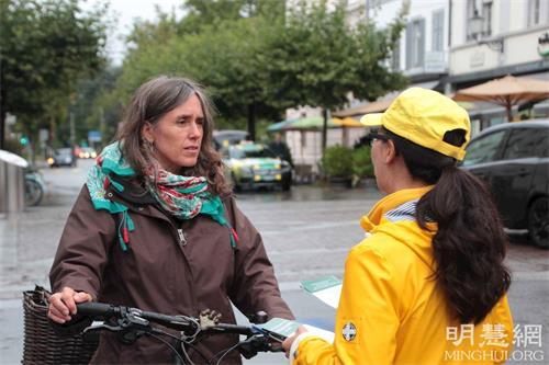 '图3:理疗师克丽丝塔(ChristaKrapfFofana,左)在温特图尔市内的格拉本广场(Grabenplatz)看到法轮功学员的功法演示,觉得很祥和,于是停下来,跟学员攀谈。'