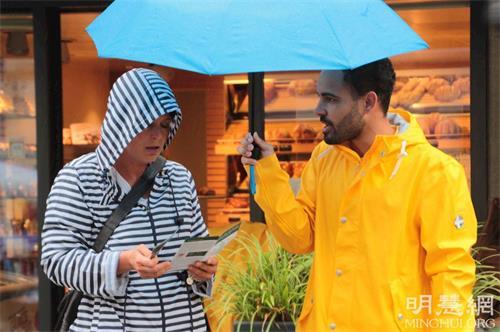 '图4:路人在雨中了解法轮功真相'