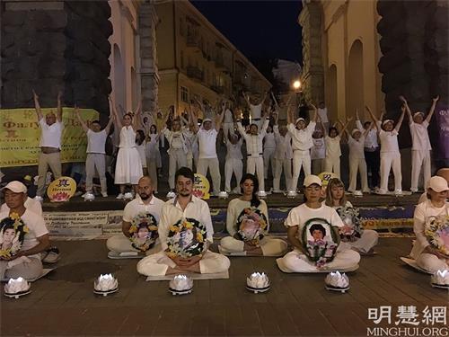 '图1:法轮功学员在市中心举行烛光悼念活动'